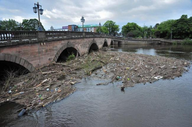 Efforts to remove the rubbish and debris from the Severn below Worcester Bridge following recent flooding.