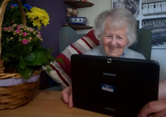 A care home resident video calling with family during the coronavirus lockdown