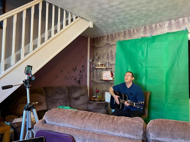 Steve Carrigan filming virtual music classes in his living room.