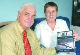 UFO enthusiasts, John Hanson and Dawn Holloway with the first instalment of Haunted Skies. Buy photo: BLB331001a