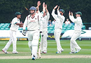 DREAM TIME: Last man Glen Chapple trudges off after being dismissed by Gareth Andrew who celebrates his third wicket in four balls during Lancashire's first innings. Picture: EMMA PERRINS