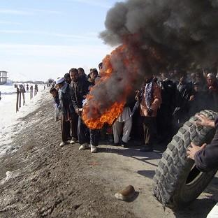 Bromsgrove Advertiser: Afghans burn tyres during an anti-US demonstration over burning of Korans at a US military base, in Logar province, Afghanistan (AP)