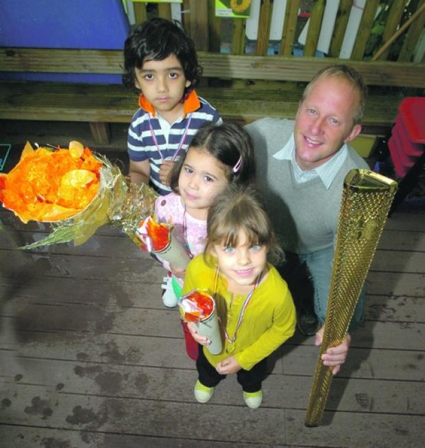 Olympic torchbearer Paul Hutchins brought along his Olympic torch to Abacus Nursery for their mini-Olympics. Pictured with youngsters Jai Badesha, Sofia Bassinder, Ellana Berry, all aged four.