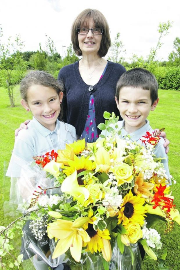 Fond farewell: Sidemoor headteacher Catherine Shearwood with pupils Kelly Munn and Sam Dipple, both aged nine. Buy photo BCR311201_a