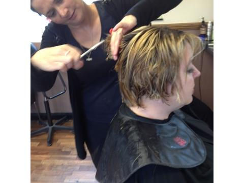 Making the cut: Salon owner Emma Parkins has her hair cut short by Natasha Smith, senior stylist at Perfections. Ref:s