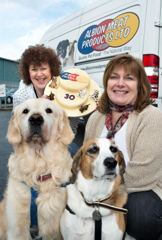 Bromsgrove Advertiser: Meaty-oric rise: Catherine Donegan with Kim Hague, who made the cake Catherine is holding, with her dogs Maisie and L