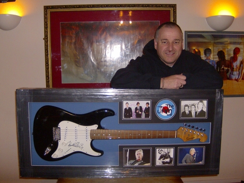 Peter Hedges from The Hop Pole with the guitar signed by music legend Paul Weller.