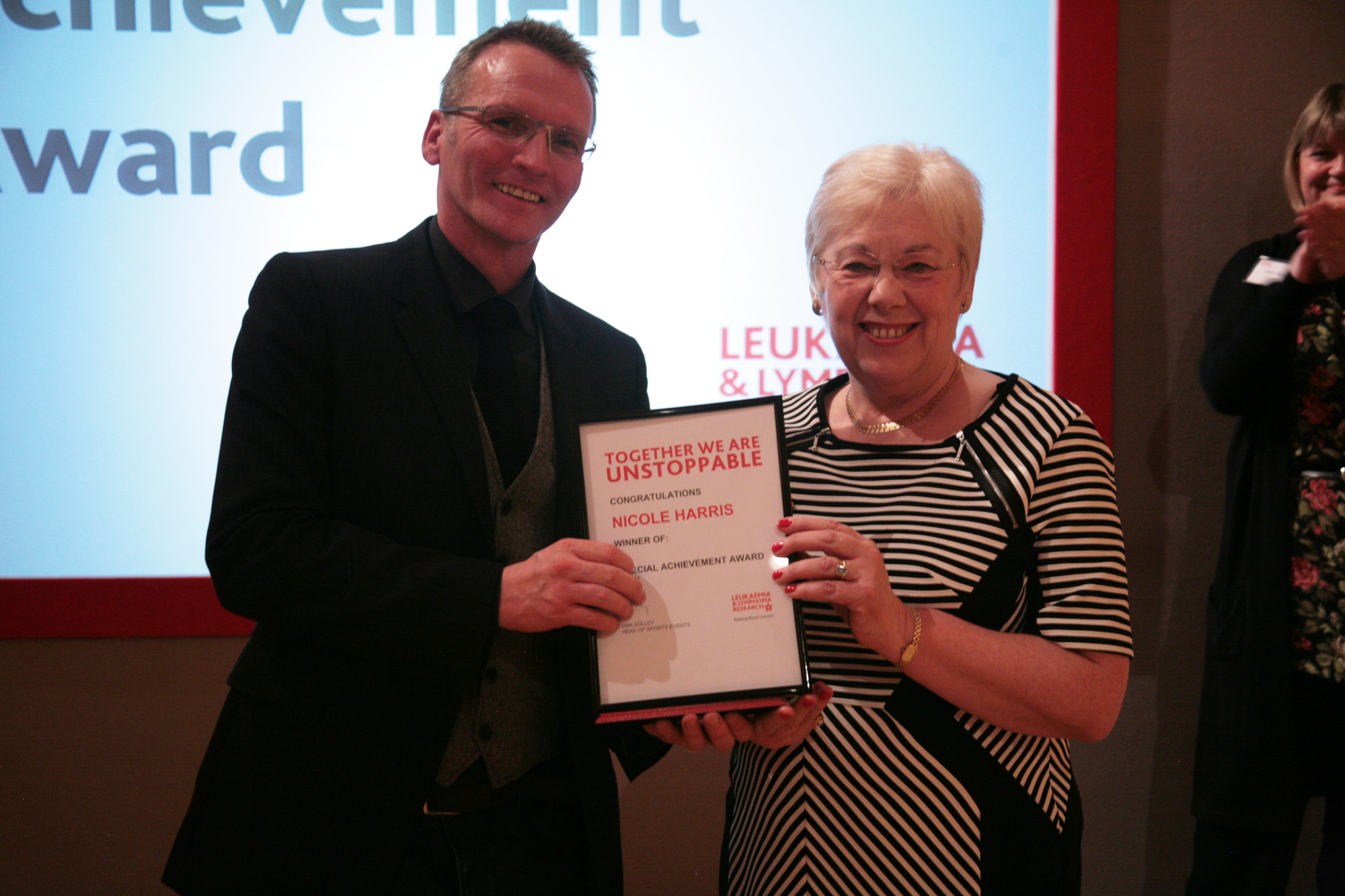 SPECIAL AWARD: Chaiman of the Bromsgrove branch of Leukaemia Research UK Nicole Harris receives a special achievement award from Barnt Green resident and former England footballer Geoff Thomas. SP