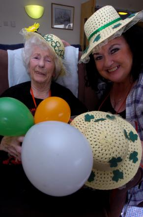 Resident Millie Cox and activities coordinator Helen Barron get ready for St Patrick's Day at Breme Care Home. Buy photo: BMM111403 at bromsgroveadvertiser.co.uk/pictures or call 01527 889030.