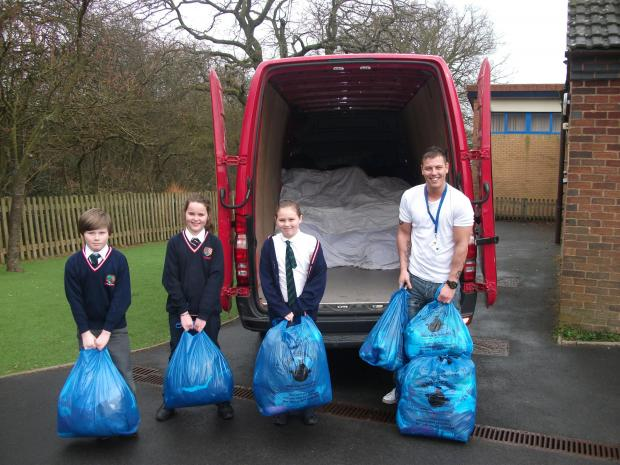 GOING GREEN: Holywell Primary and Nursery School youngsters Charlie Bayliss, Romany Parker and Niamh Bayliss make a donation to Bag2School UK. SP