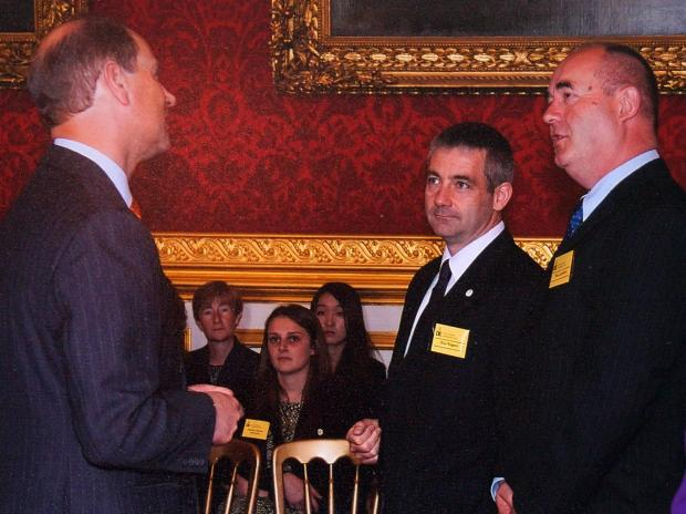 RECOGNITION: Ron Jackson, right, and Guy Rogers, centre, receiving their awards from Prince Edward.