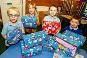 Play N Discover Pre-School children have been putting together Christmas charity shoeboxes for children around the round. Pictured are Lewis Rogers, four, Emilia Baylis, three, Evie-Jean Caffull, three, and Harry Smith, three. Buy photo  BCR471401_01