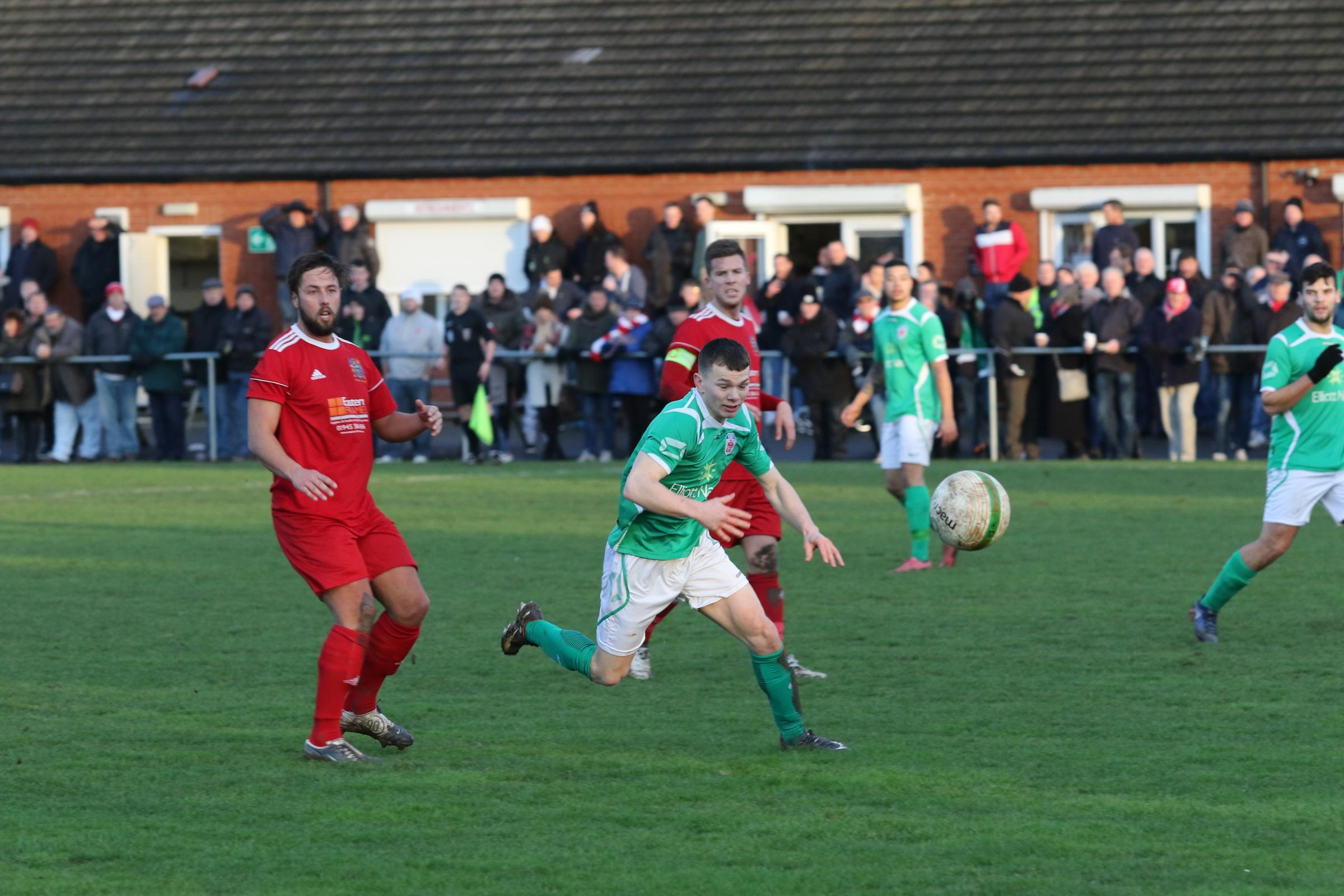 Jason Cowley battles for the ball against Wisbech. Photo by David Besley.