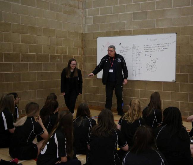 Pete Martin, with rubber knife, talking to school pupils